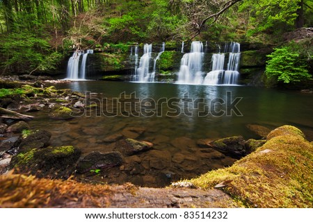Spring cascades at Sgwd y Pannwr in Brecon Beacons national park, Wales, with mossy log in the foreground. - stock photo