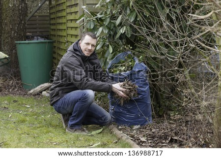 spring cleaning in the garden.   young gardener at work. - stock photo