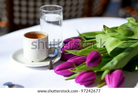 Spring coffee. Cup of fresh espresso and bunch of beautiful tulips - stock photo