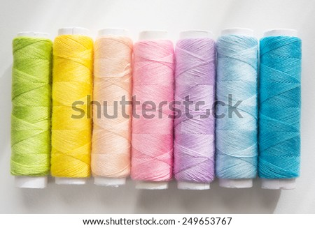 Spring colors. Light colored sewing threads on a white table with warm spring sunlight by the window . - stock photo