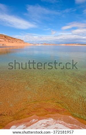 Spring Desert Lake - Vertical - The spring sun shines on the colorful Lake Powell. Glen Canyon National Recreation Area, Page, Arizona, USA. - stock photo