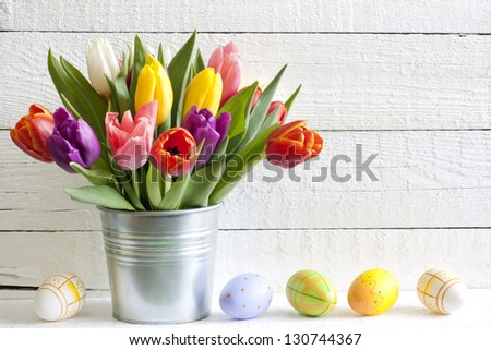 Spring easter tulips in bucket on white vintage planks - stock photo