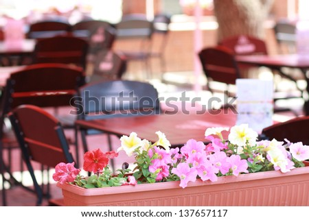 spring empty outdoor cafe in early morning focus on flowers - stock photo