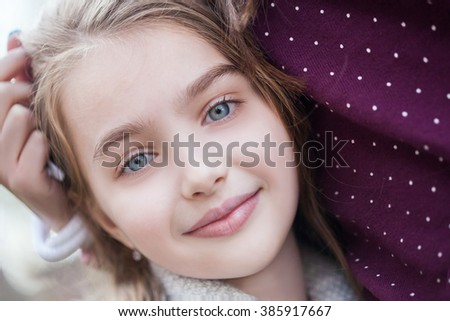 Spring fairy. Portrait of beautiful little smiling girl with brownish blond hair and blue eyes. - stock photo