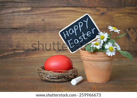 Spring flowers, Easter egg and Happy Easter sign on wooden table - stock photo