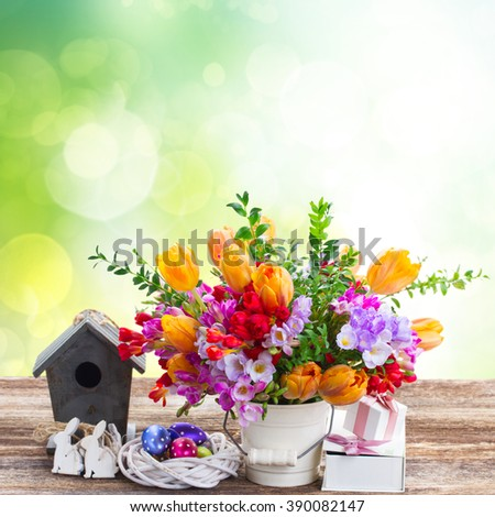 Spring fresh blooming  flowers with easter eggs and bunny on wooen table over green garden background - stock photo