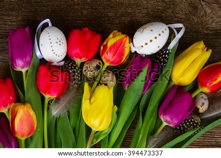 Spring fresh  flowers with easter eggs  and feathers on wooden table  - stock photo