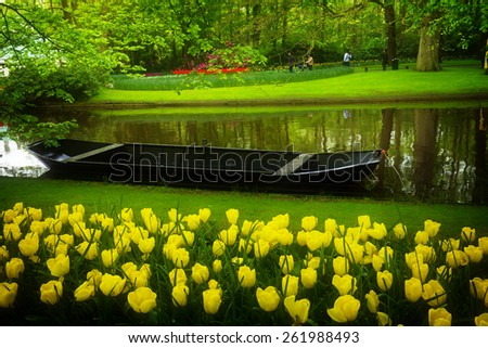 spring garden with  water canal and boat,   'Keukenhof', Holland, retro toned - stock photo