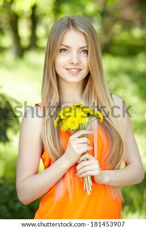 Spring girl. Lovely blond girl with bunch of dandelions outdoors looking up - stock photo