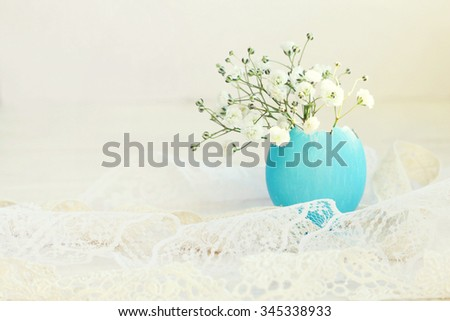 Spring home decor - tiny egg shell vase, turquoise painted, delicate flower. Soft light, soft focus,toned. - stock photo