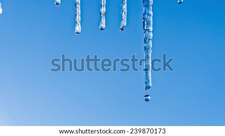 Spring icicle thawing on blue sky - stock photo
