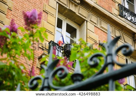 Spring in Paris. Blossoming lilac flowers and typical Parisian building with French flag hanging out from the window. Selective focus on the building. - stock photo