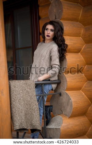 Spring in the country style. Full length portrait of young woman in white knitted sweater and furry hat standing in the front of rustic wood wall in the yard near house, wearing sweater - stock photo