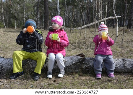 Spring in the pine forest sitting on a log and three small children drink tea from colored cups. - stock photo