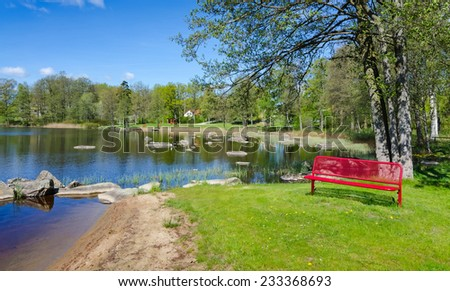 Spring lake panorama landscape with symbolic red bench - stock photo