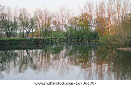 spring landscape sunset on the river near the oak grove - stock photo