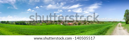 Spring landscape with green grass, village, road and clouds - stock photo