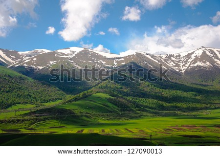 Spring landscape with snowy mountains - stock photo