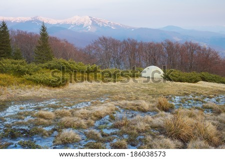 Spring landscape with tourist tent in the mountains. Mountain stream of melted snow. Carpathians, Ukraine, Europe - stock photo