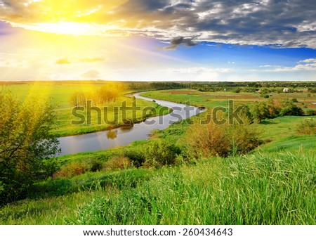 Spring meadow, meandering river, bright sun and blue sky in the evening. - stock photo