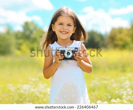 Spring mood. Sunny portrait smiling child with old retro vintage camera having fun outdoors in warm good day - stock photo