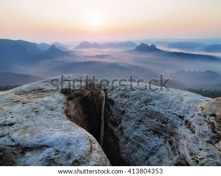 Spring morning mist. The sandstone cliff above forest valley, daybreak Sun at horizon. Hills increased from foggy background - stock photo