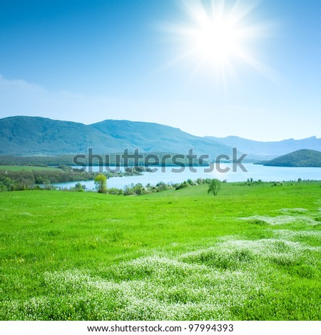 Spring mountain landscape with a lake and meadow - stock photo