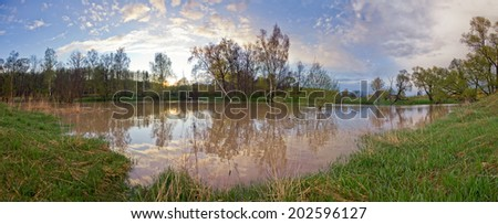Spring panorama with the river in flood at sunset - stock photo