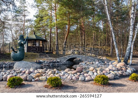 Spring park decorated with stone bridge and statue of Poseidon - stock photo