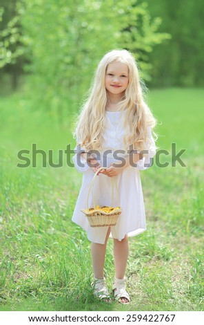 Spring portrait of cute little girl in white dress with long blonde hair holding a basket of yellow dandelions on a nature  - stock photo