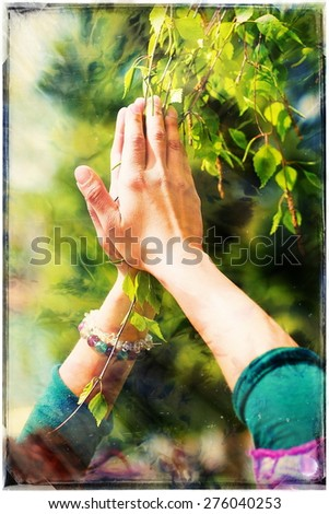 Spring prayer â?? adoring the healing powers of the spring. Tree in hands, with color pattern. - stock photo