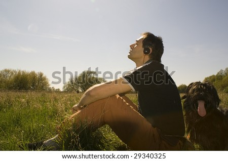 Spring relax on the meadow with msuic on - stock photo