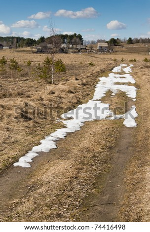 Spring road leading into the village - stock photo
