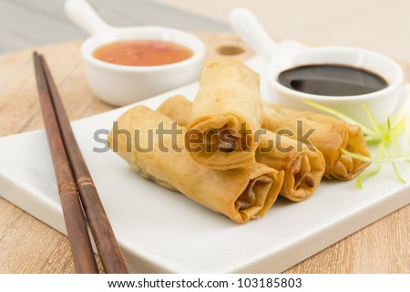 Spring Rolls - Fried duck spring rolls served with soy sauce and sweet chili dip. - stock photo