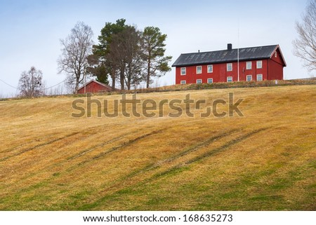 Spring rural Norwegian landscape with red house and field - stock photo
