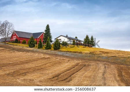 Spring rural Norwegian landscape with wooden houses and empty dry field - stock photo