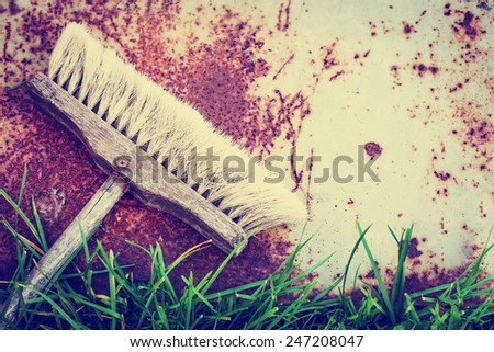 Spring rustic background with vintage brooms and green grass/ Spring cleaning concept - stock photo