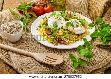 Spring salad from lentils, fresh herbs, baked nuts and on the top delicious poached egg - bio eggs, healthy and fresh - stock photo