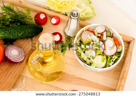 Spring salad with radishes, cucumber, Chinese cabbage and red onion closeup vsteklyannoy bowl on a white wooden background - stock photo