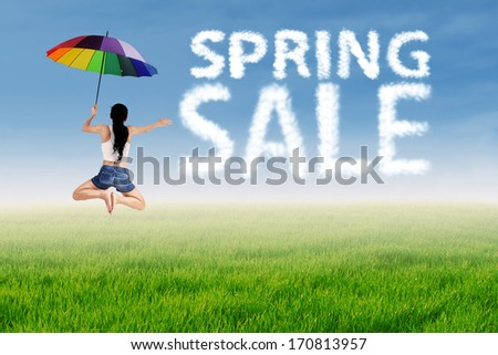 Spring sale clouds and woman jumping over green meadow - stock photo