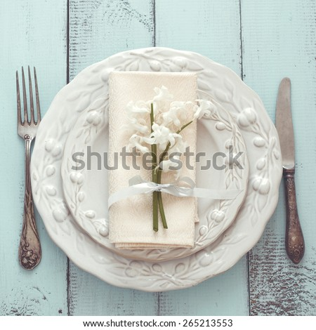 Spring shabby chic table setting on mint wooden background, top view point - stock photo