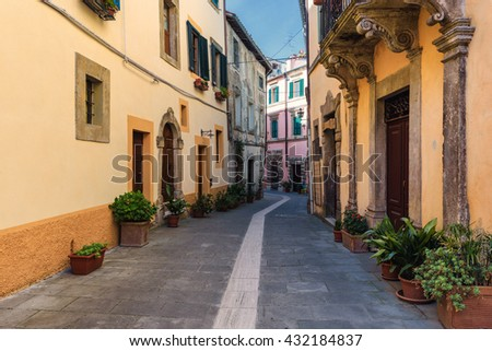 Spring streets of the old Tuscan town. Colorful flowers bloom and fragrant. - stock photo