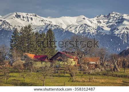 Spring sunny rural landscape with snowy Bucegi mountains and traditional Romanian houses and farm in Predelut village, near Bran, Transylvania region, Romania. - stock photo