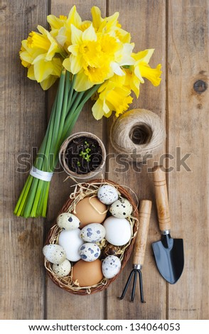 Spring symbols - daffodils, basket with eggs and gardening tools on a wooden table - stock photo