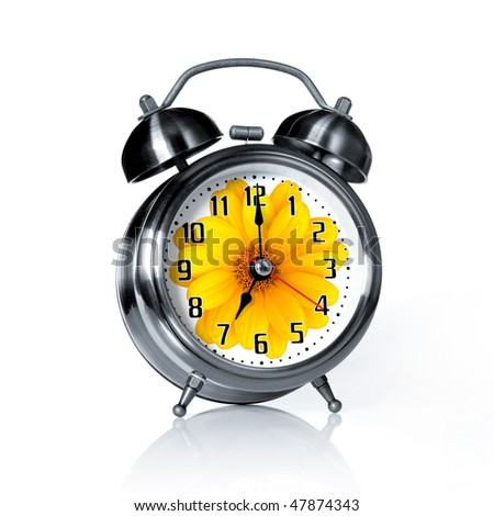 Spring time old fashion alarm clock with a printed flower - stock photo