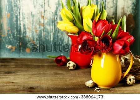 Spring tulips in vases and easter eggs  on wooden table - spring, easter or gardening concept - stock photo