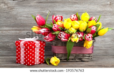 spring tulips in wooden basket, red polka-dot gift box. happy mothers day, romantic still life, fresh flowers. on wooden background - stock photo