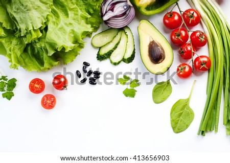 Spring vegetable background. Juicy fresh spring vegetables and herbs, such as cherry tomatoes, lettuce, spinach, cucumber slices and stuff on a white background. Place for writing text or recipe - stock photo