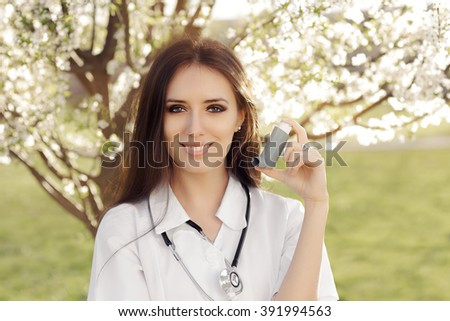 Spring Woman Doctor Smiling and Holding Inhaler - Portrait of female medical professional with an asthma remedy in springtime décor  - stock photo