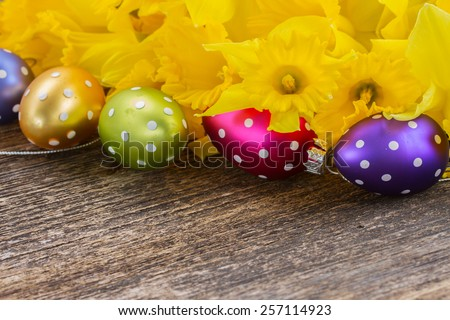 spring yellow daffodils with easter eggs border on wooden background - stock photo